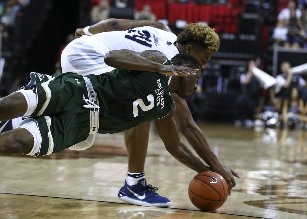 UNR guard Jordan Caroline (24) and Colorado State forward Emmanuel Omogbo (2) fight for a loose ball during the Mountain West Conference basketball championship game at the Thomas & Mack Cente ...