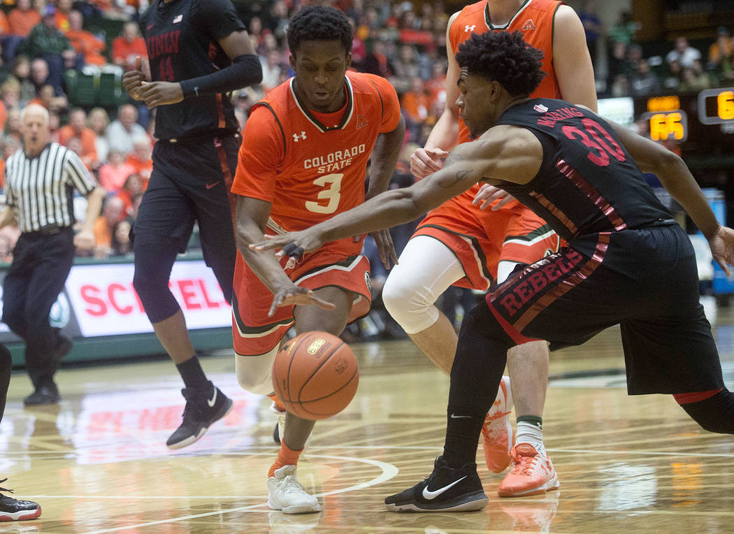 Colorado State guard Raquan Mitchell keeps control of the ball as UNLV guard Jovan Mooring, right, reaches for it during an NCAA college basketball game Saturday, Jan. 20, 2018, in Fort Collins, C ...