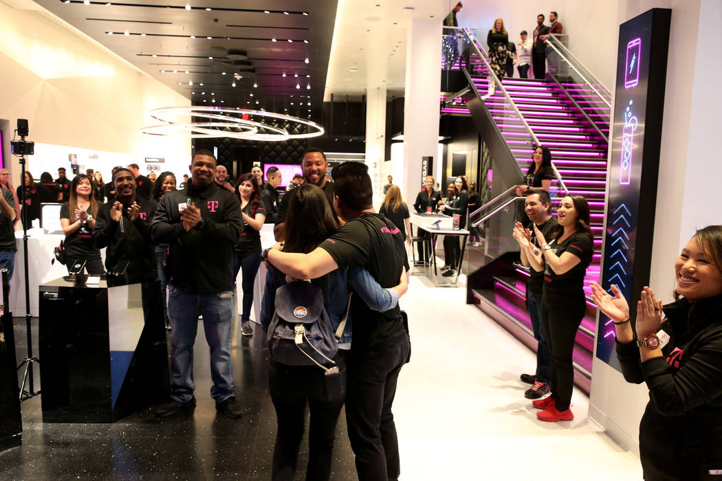 T-Mobile Signature Mobile Expert Lance Tran, center, hugs one of the first customers on opening night of the nightclub-themed signature store on the Strip Thursday, Jan. 4, 2018. It is located ins ...