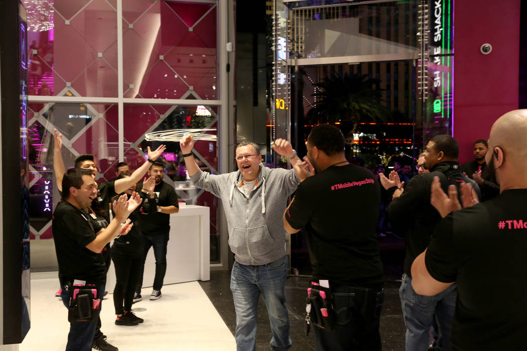T-Mobile employees cheer one of the first customers opening night of the nightclub-themed signature store on the Strip Thursday, Jan. 4, 2018. It is located inside the Showcase Mall, near the inte ...