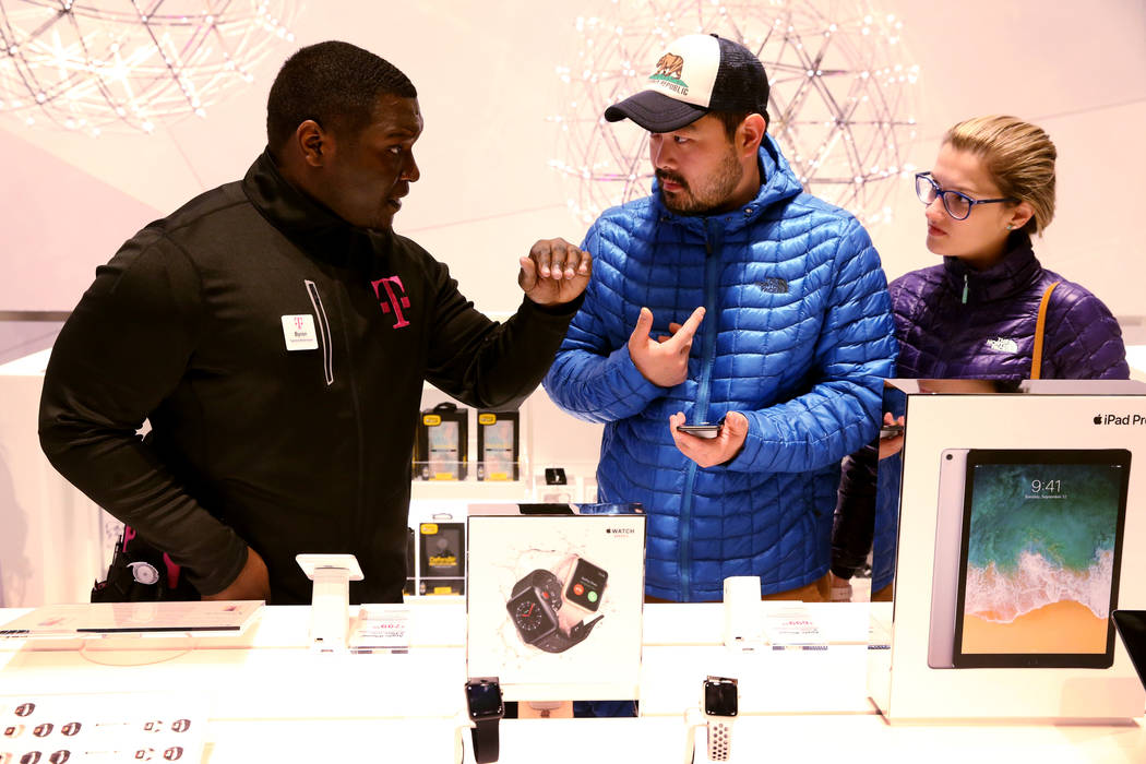 T-Mobile Signature Mobile Expert Byron Stewart, left, helps Raneto Watanabe, center, and Andreya Furreil of Brazil on opening night of the nightclub-themed signature store on the Strip Thursday, J ...