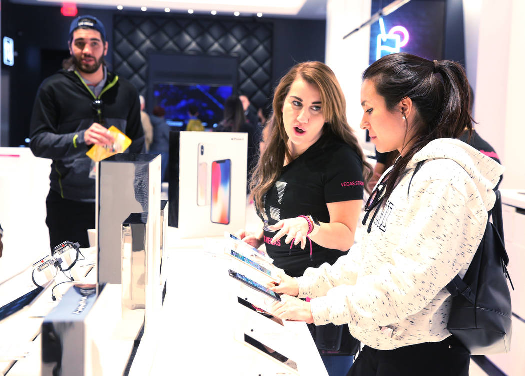 T-Mobile Signature Mobile Expert Dulce Rodriguez, center, helps Samantha Rada of Charlotte, N.C., on opening night of the nightclub-themed signature store on the Strip Thursday, Jan. 4, 2018. It i ...