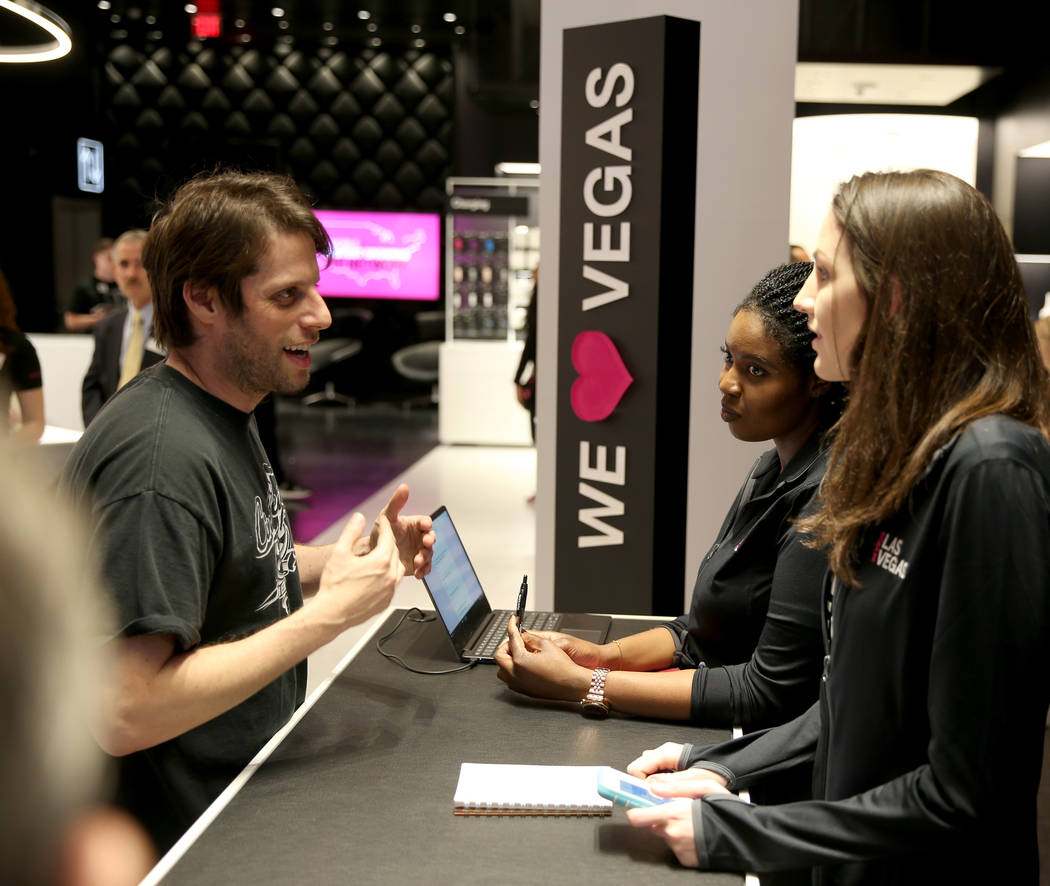 The T-Mobile employees Fatou Niang, center, and Kelly Fisher, talk to Jonathan Finkel on opening night Thursday, Jan. 4, 2018. It is located inside the Showcase Mall, near the intersection of Las  ...