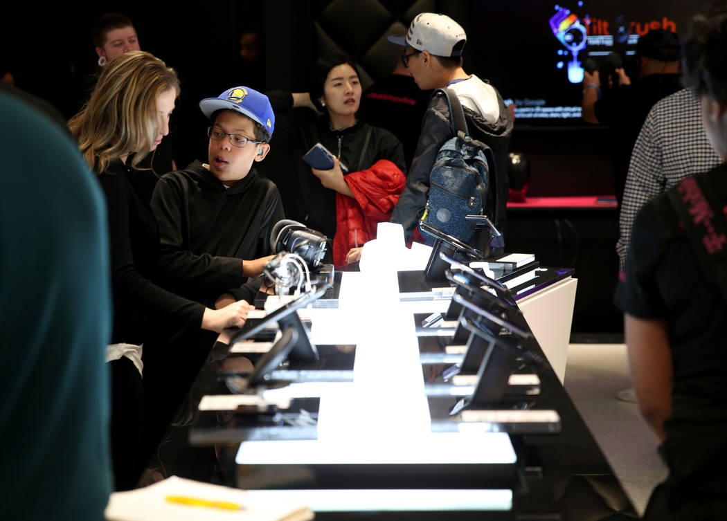 Jalen Roberts, 11, second from left, and his mother Brandy Roberts check out virtual reality goggles at the T-Mobile store on the Strip on opening night Thursday, Jan. 4, 2018. It is located insid ...