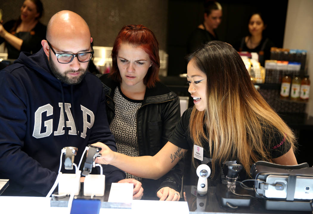 Ernesto Mendoza and Claudia Aguilera of Las Vegas, left, check out smart watches with T-Mobile Signature Mobile Expert Hellen Sengaroun store on opening night of the Strip store Thursday, Jan. 4,  ...