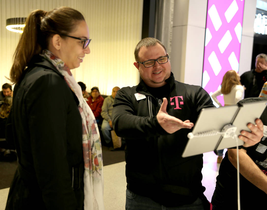 T-Mobile Signature Mobile Expert Shane Butts helps Jessica Spear of Brazil on opening night of the Strip store Thursday, Jan. 4, 2018. It is located inside the Showcase Mall, near the intersection ...