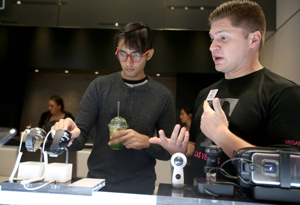 Yustynn Panicker of Singapore, left, checks out smart watches with the help of Signature Mobile Expert Mick Jones on opening night of the nightclub-themed T-Mobile store on the Strip Thursday, Jan ...