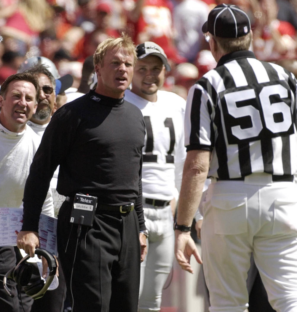 Oakland Raiders coach Jon Gruden, left, asks for an explanation of a call from line judge Ron Baynes (56) during the third quarter against the Kansas City Chiefs in Kansas City, Mo., Sunday, Sept. ...