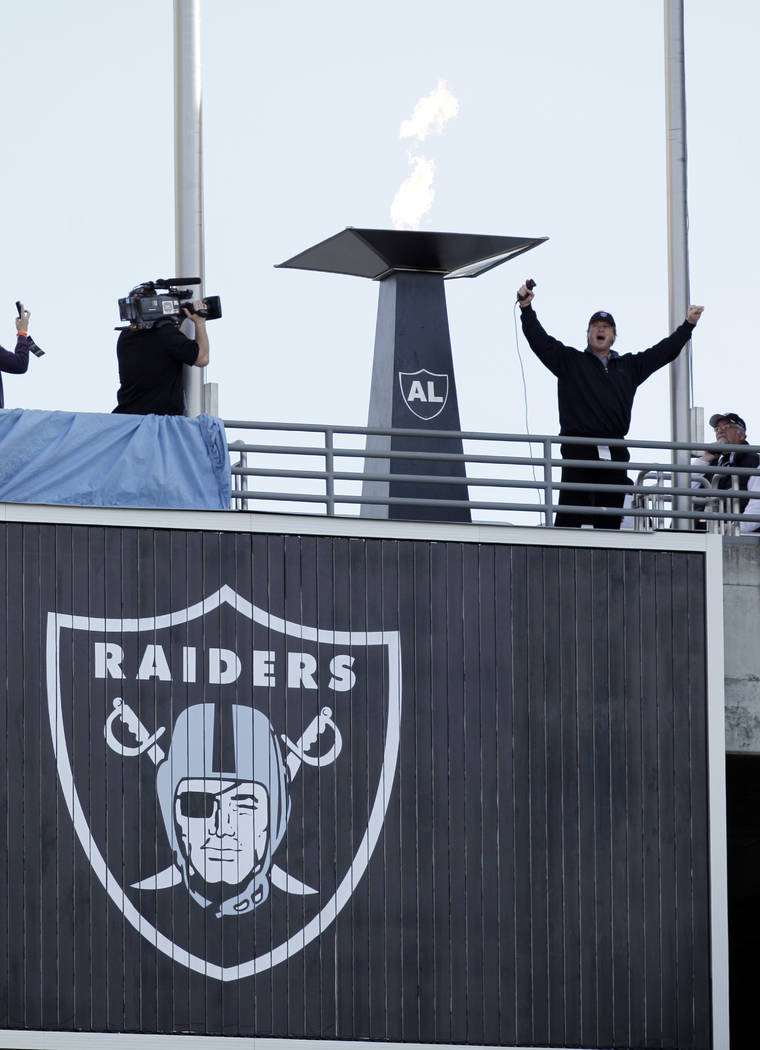 Former Oakland Raiders head coach John Gruden lights a torch before an NFL football game against the New Orleans Saints in Oakland, Calif., Sunday, Nov. 18, 2012. (AP Photo/Ben Margot)
