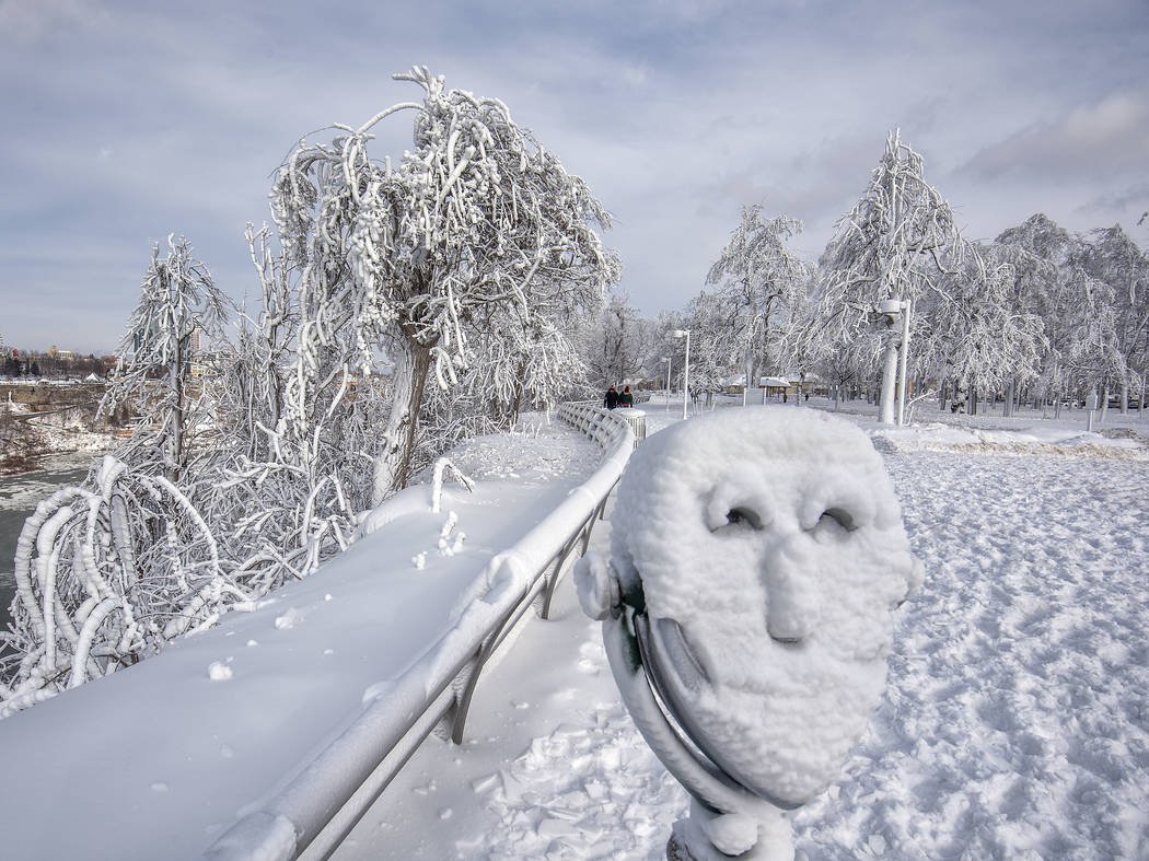 A coin operated binocular is covered with snow on Goat Island at Niagara Falls State Park in Niagara Falls, N.Y., Tuesday, Jan. 2, 2018. Almost every year frigid temperatures transform Niagara Fal ...