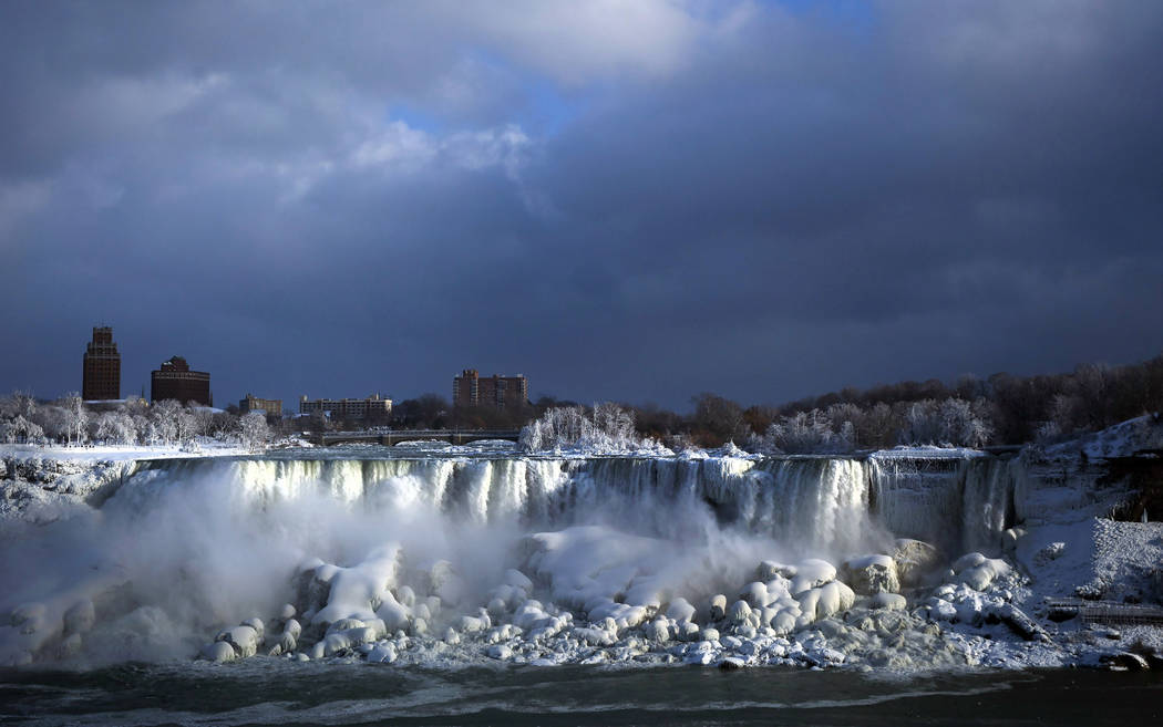 Water flows over the American Falls as ice forms in this view from the Canadian side in Niagara Falls, Ont., Tuesday, Jan. 2, 2018.  Almost every year frigid temperatures transform the falls into  ...