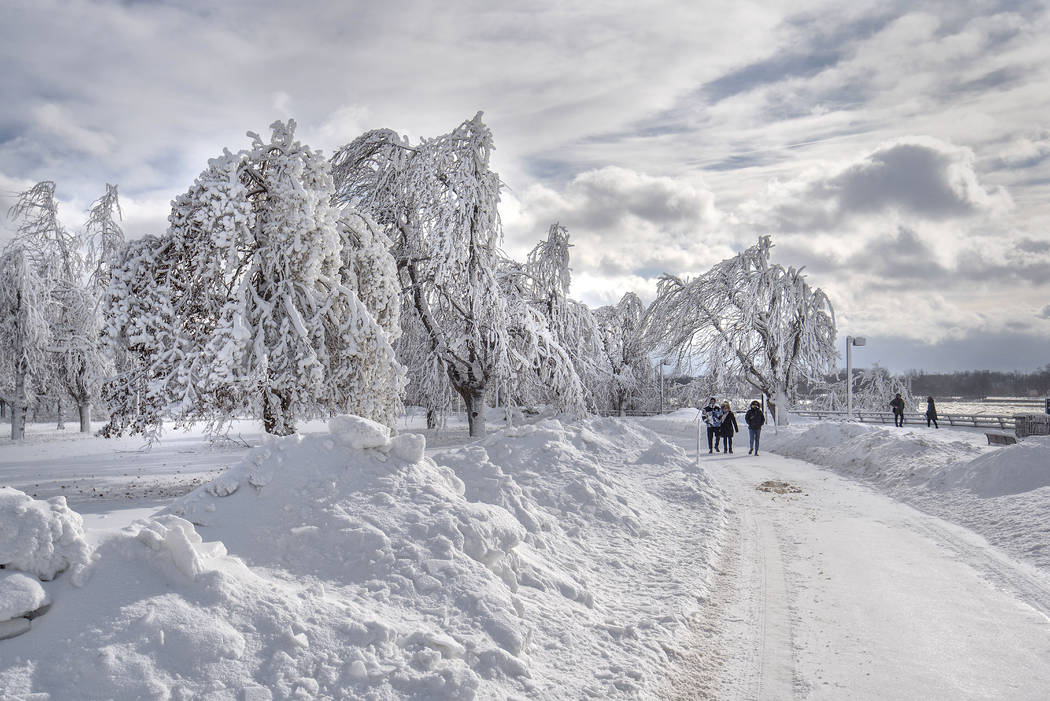 Visitors walk at a frozen Niagara Falls in views from Stedman's Bluff on Goat Island of the American Falls. Visitors to Goat Island at Niagara Falls State Park are treated to a winter wonderland w ...