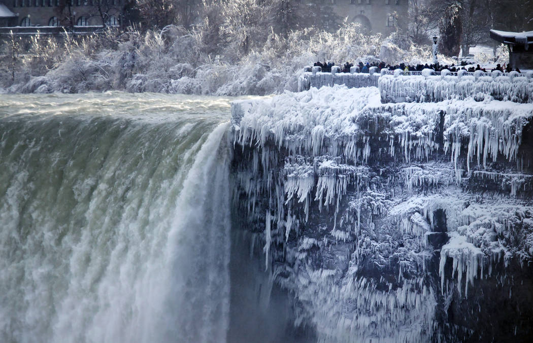 Visitors take photographs at the brink of the Horseshoe Falls in Niagara Falls, Ont., Tuesday, Jan. 2, 2018.  Almost every year frigid temperatures transform the falls into an icy winter wonderlan ...