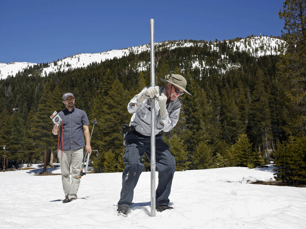 File - In this May 1, 2017 file photo, Frank Gehrke, chief of the California Cooperative Snow Surveys Program for the Department of Water Resources, right, plunges the snow survey tube into the sn ...