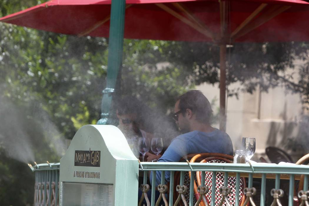 Tourists are seen on a hot day through misters as they sit outside Mon Ami Gabi restaurant at Paris Las Vegas on the Las Vegas Strip. The National Weather Service says 2017 is ranked as the warmes ...