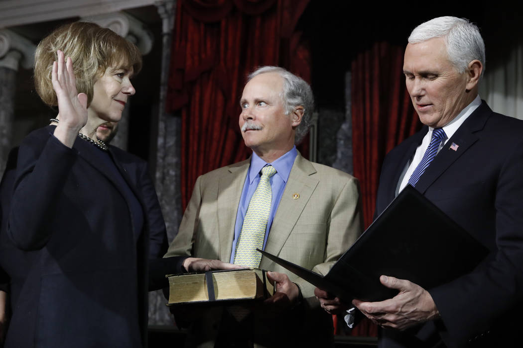 Vice President Mike Pence, right, administers the Senate oath of office during a mock swearing in ceremony in the Old Senate Chamber to Sen. Tina Smith, D-Minn., left, with her husband Archie Smit ...