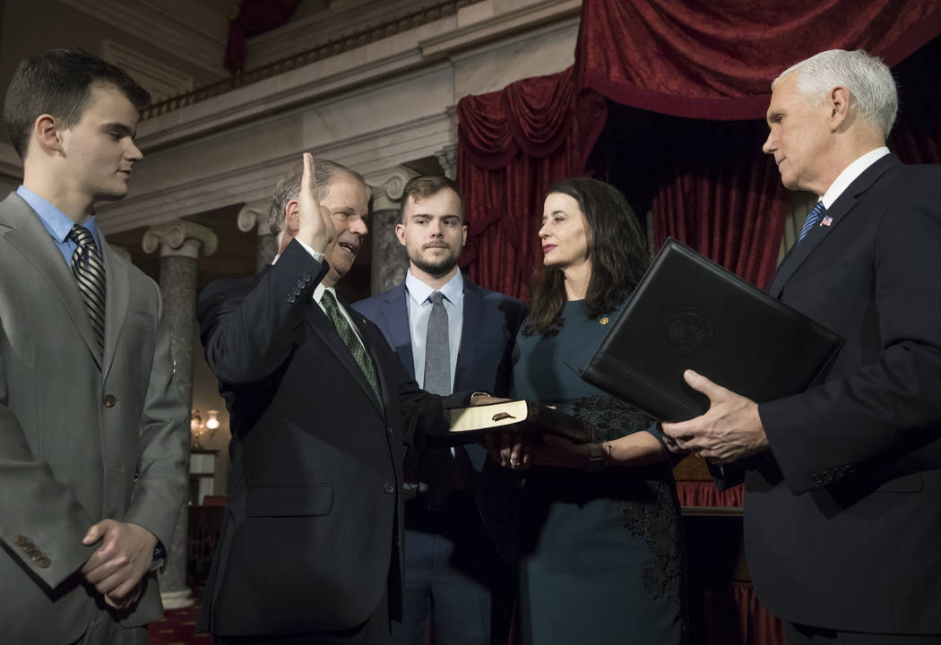 Vice President Mike Pence, right, administers the Senate oath of office during a mock swearing in ceremony in the Old Senate Chamber to Sen. Doug Jones, D-Ala., second from left, with his wife, Lo ...