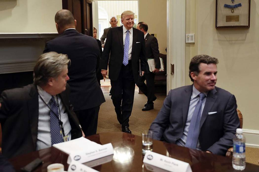 President Donald Trump smiles as he walks in from the Oval Office of the White House in Washington on Jan. 23, 2017, to host breakfast with business leaders in the Roosevelt Room. Sitting at the t ...