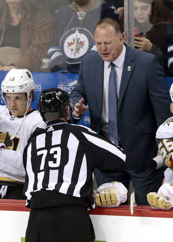 Dec 1, 2017; Winnipeg, Manitoba, CAN;  Vegas Golden Knights Head Coach Gerard Gallant talks with Linesman Vaughan Rudy during a stop in play in the first period at Bell MTS Place. (James Carey Lau ...