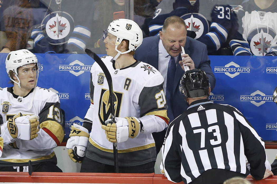 Las Vegas Golden Knights head coach Gerard, upper right, Gallant talks to a linesman (73) during first-period NHL hockey game action against the Winnipeg Jets in Winnipeg, Manitoba, Friday, Dec. 1 ...