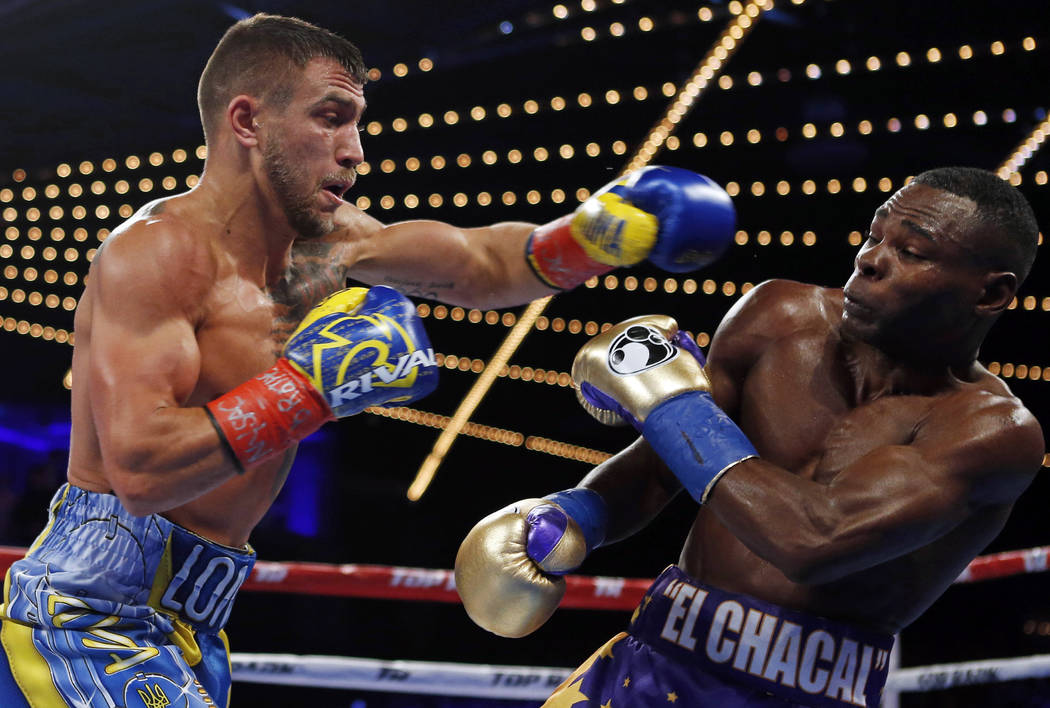 Vasyl Lomachenko punches Guillermo Rigondeaux during the third round of a WBO junior lightweight title boxing match Saturday, Dec. 9, 2017, in New York. (AP Photo/Adam Hunger)