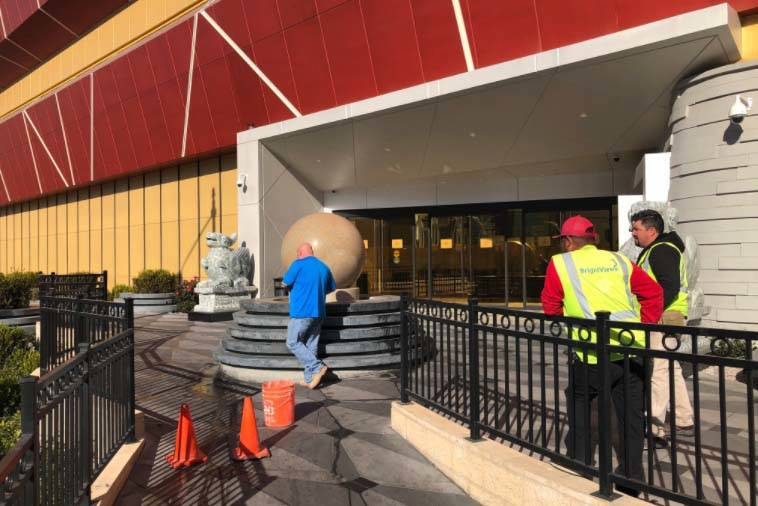 Construction workers turn off the water-spinning stone ball outside the Lucky Dragon Thursday morning, Jan. 4, 2018. The hotel-casino posted signs saying the casino has been closed. The hotel rema ...