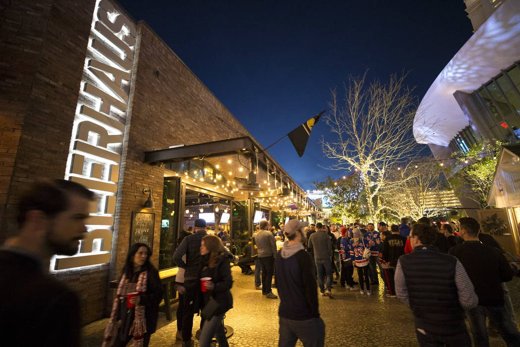 Hockey fans walk past Beerhaus at The Park ahead of NHL hockey game between the Vegas Golden Knights and the New York Rangers at the T-Mobile Arena in Las Vegas, Sunday, January 07, 2018. Richard  ...
