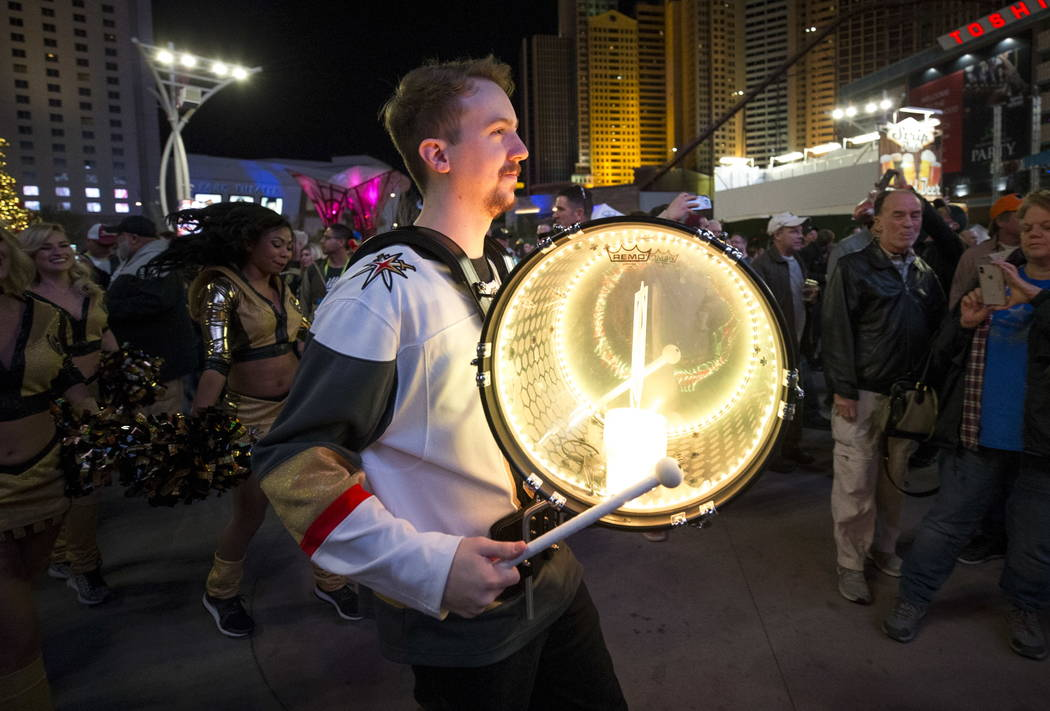 A member of the Knight Line marching band parades with Knights mascot Chance the Golden Gila Monster and the ice girls ahead of NHL hockey game between the Vegas Golden Knights and the New York Ra ...