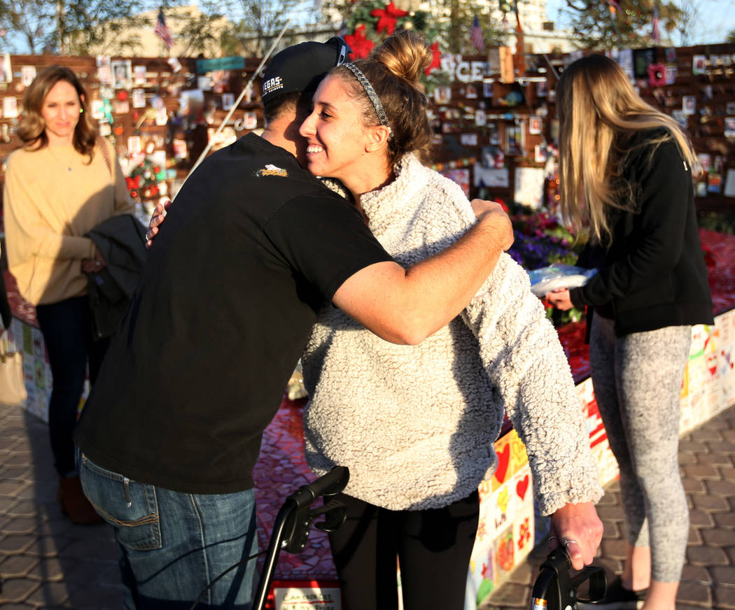 Katrina Hannah, 21, of La Verne, Calif., hugs Austin Stout, of Las Vegas, who carried her to safety after she was shot at the Route 91 Harvest festival during a visit to the Healing Garden in down ...