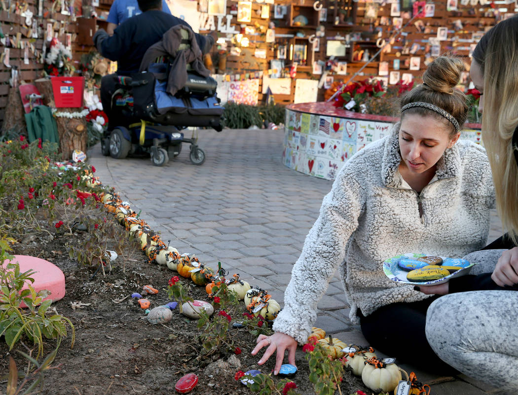 Katrina Hannah, 21, of La Verne, Calif., who was shot at the Route 91 harvest festival country music concert, places rocks during a visit to the Healing Garden in downtown Las Vegas Thursday, Jan. ...