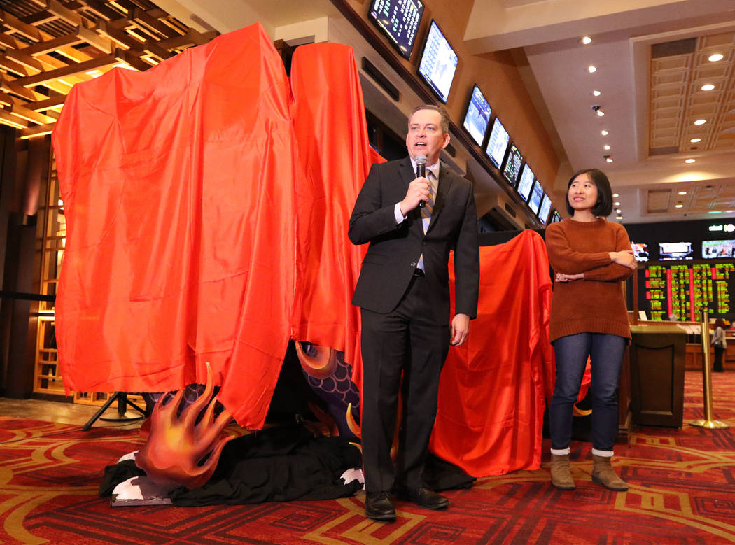 Sichuan Tianyu Culture Communication Co., Ltd. event manager Huiyuan Liu, right, and Boyd Gaming vice president of corporate communications David Strow prepare to unveil a life-size Kylin Lantern  ...