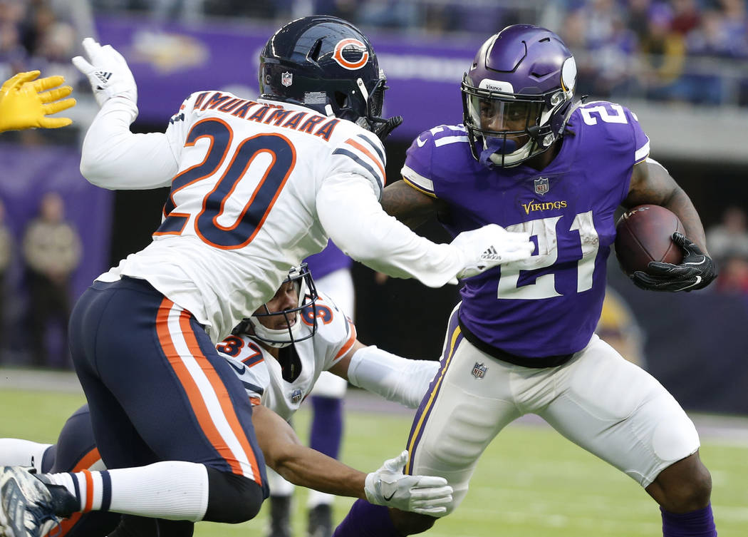 Minnesota Vikings running back Jerick McKinnon (21) breaks a tackle by Chicago Bears cornerback Prince Amukamara (20) and Bryce Callahan (37) during the first half of an NFL football game, Sunday, ...