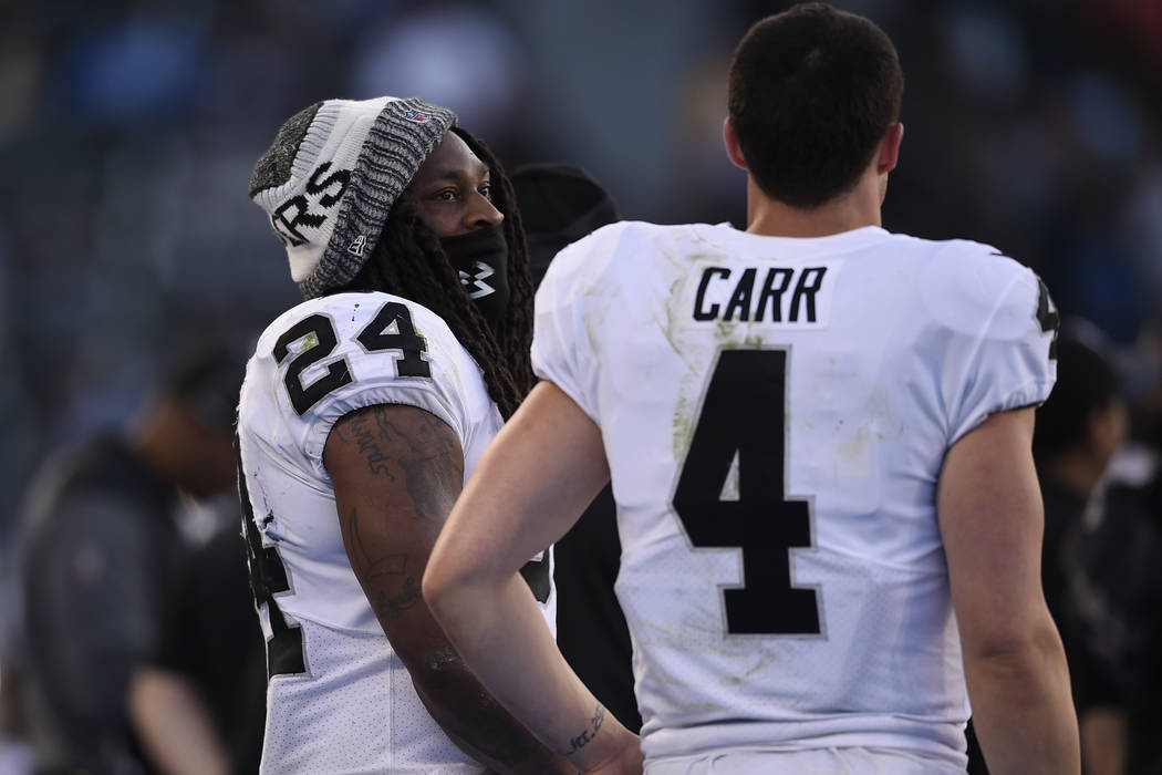 Oakland Raiders running back Marshawn Lynch, left, speaks with quarterback Derek Carr during the second half of an NFL football game against the Los Angeles Chargers, Sunday, Dec. 31, 2017, in Car ...