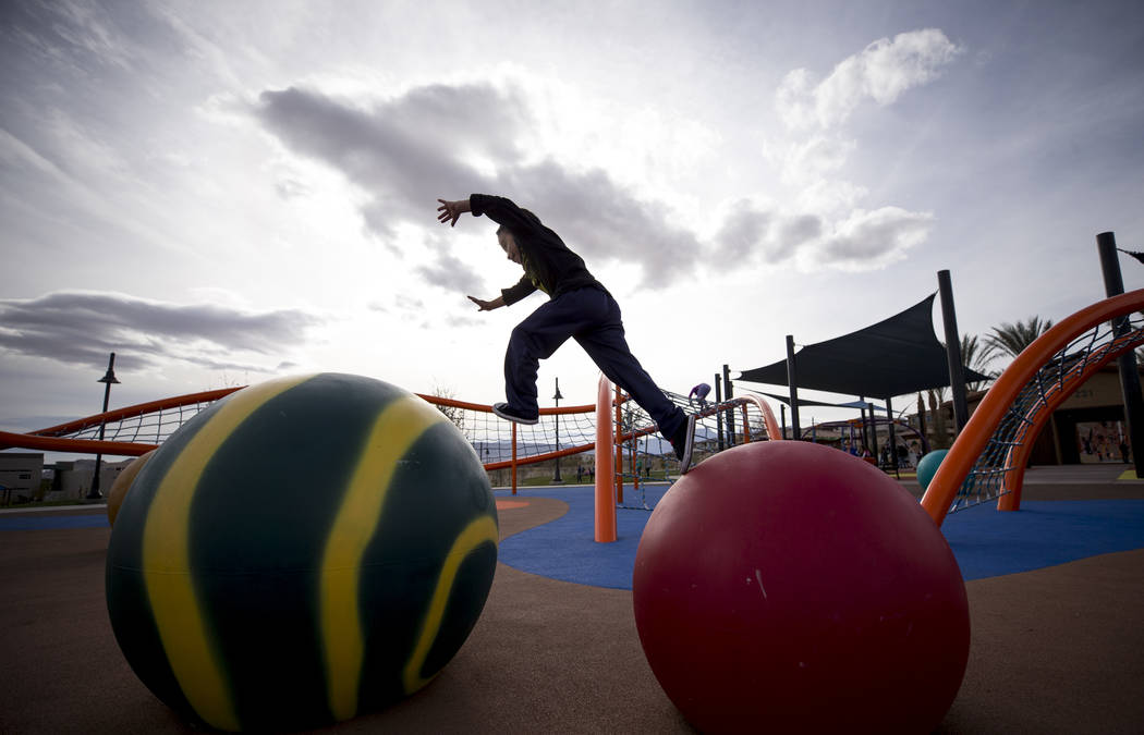 Five-year-old Kroy Goodwin of Las Vegas leaps from a giant colorful climbing ball to another while playing at Summerlin's Fox Hill Park in The Paseos village neighborhood, Saturday, Jan. 6, 2018,  ...