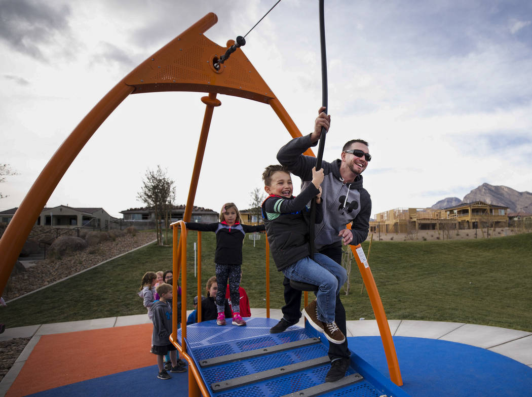 Las Vegas resident Phil Nicholson pushes his son Drew, 5,  on a zip line ride at Summerlin's Fox Hill Park in The Paseos village neighborhood, Saturday, Jan. 6, 2018, in Las Vegas. Richard Brian L ...