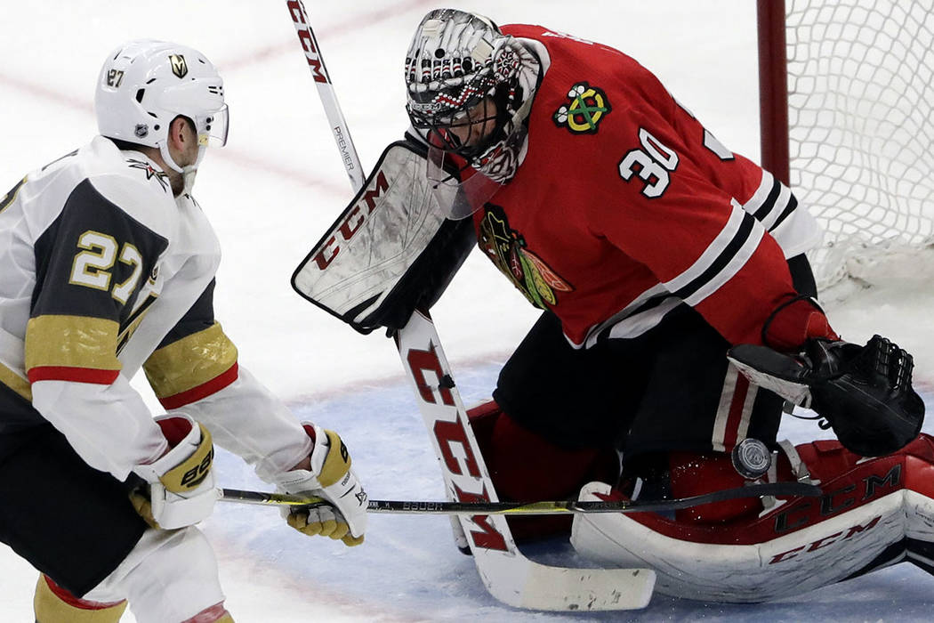Chicago Blackhawks goalie Jeff Glass, right, blocks a shot by Vegas Golden Knights defenseman Shea Theodore during the third period of an NHL hockey game Friday, Jan. 5, 2018, in Chicago. (AP Phot ...