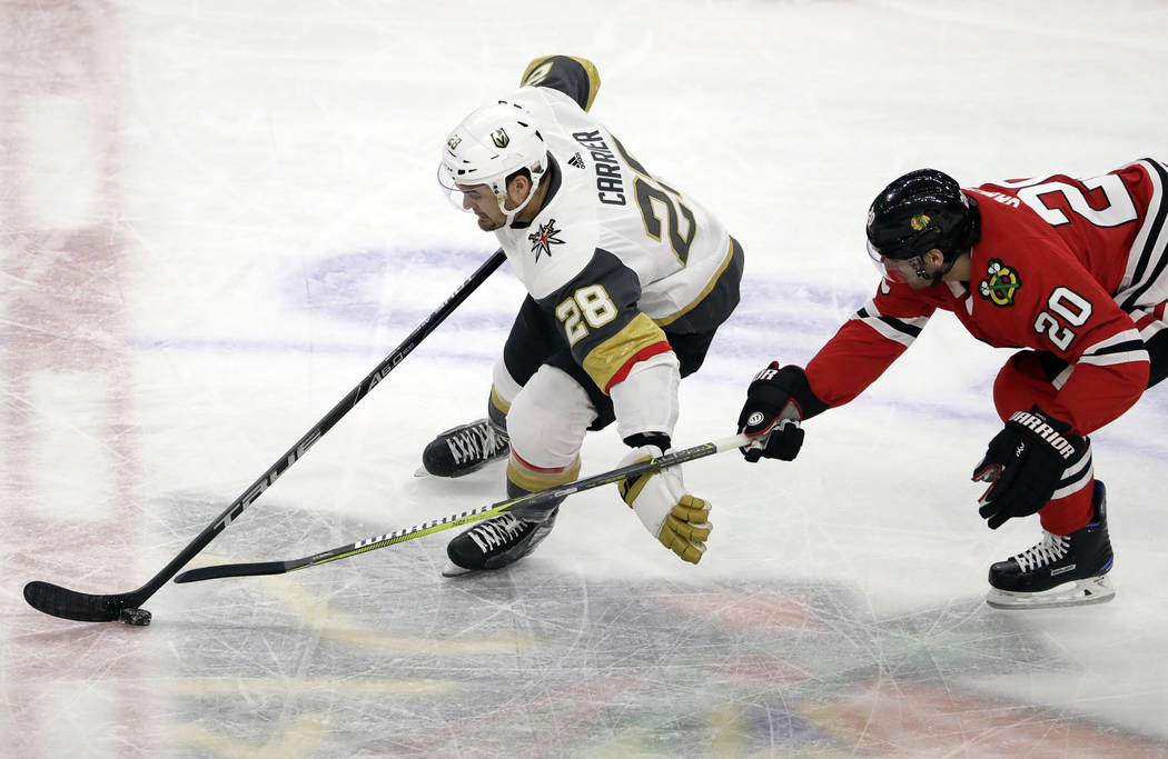 Vegas Golden Knights left wing William Carrier, left, controls the puck against Chicago Blackhawks left Brandon Saad during the second period of an NHL hockey game Friday, Jan. 5, 2018, in Chicago ...
