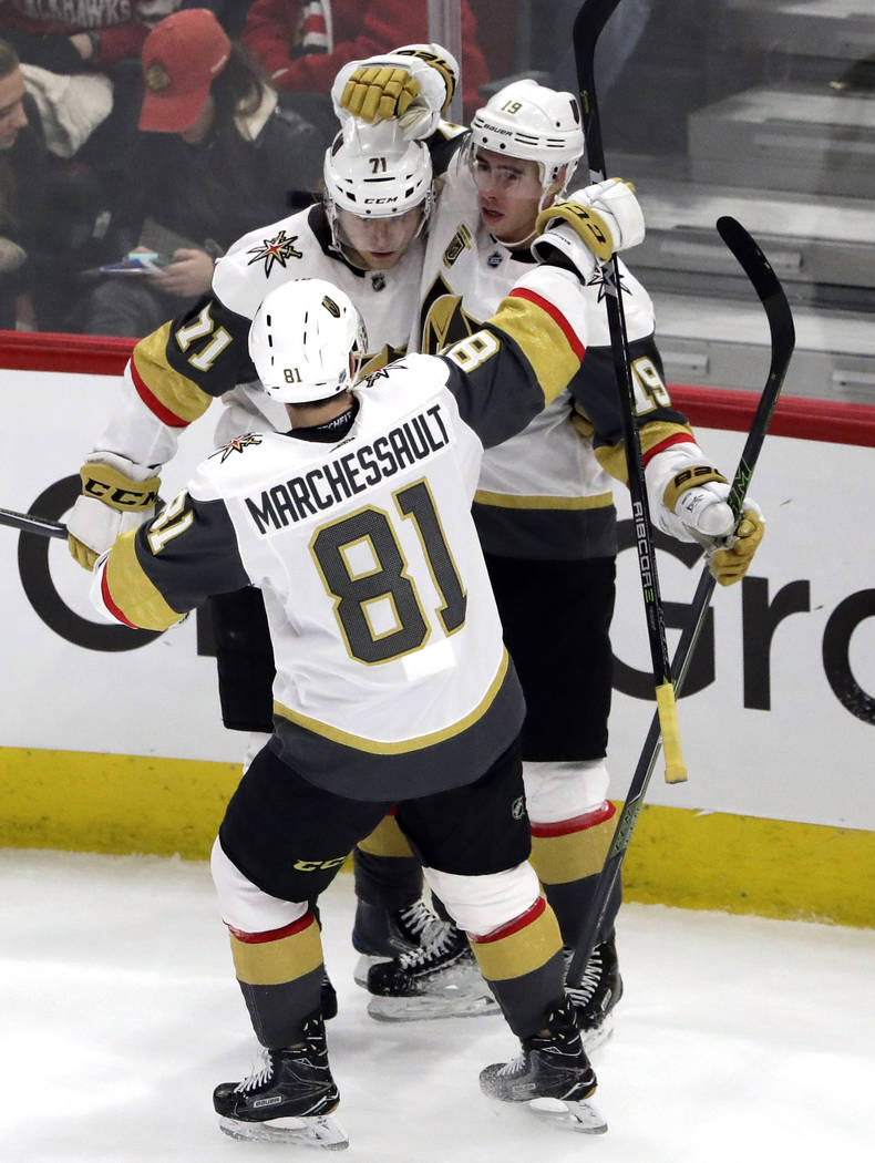 Vegas Golden Knights right wing Reilly Smith (19) celebrates with centers William Karlsson, left, and Jonathan Marchessault after scoring a goal against the Chicago Blackhawks during the third per ...