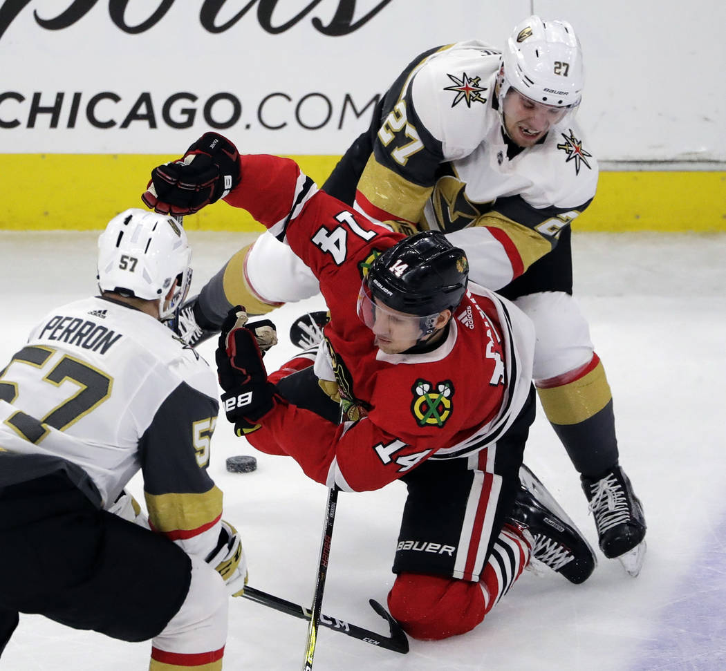 Chicago Blackhawks right wing Richard Panik, center, battles for the puck against Vegas Golden Knights left wing David Perron, left, and defenseman Shea Theodore during the third period of an NHL  ...
