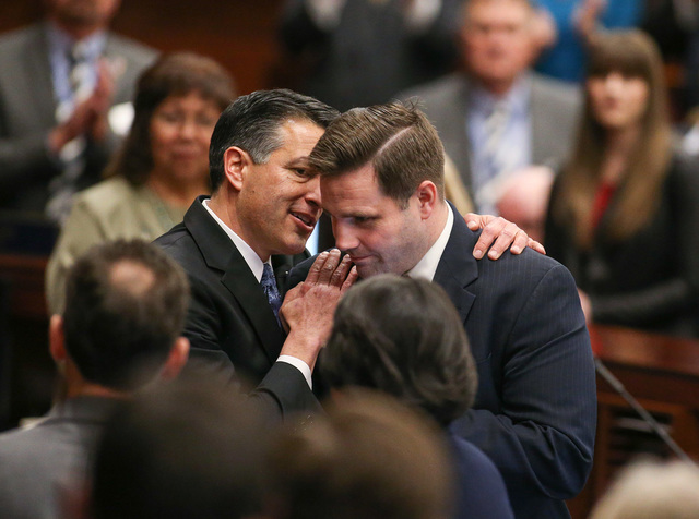 Gov. Brian Sandoval stops for a quick word with then-Director of Military and Veterans Policy Caleb Cage following his State of the State address at the Legislative Building in Carson City, Nev.,  ...