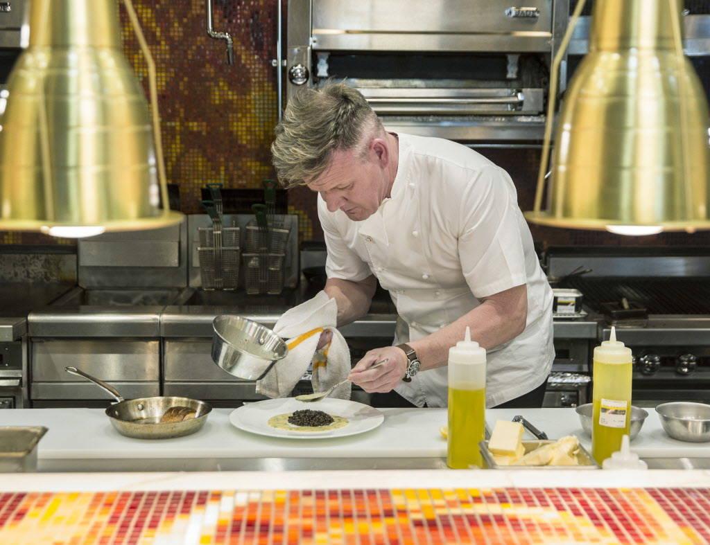 Celebrity chef Gordon Ramsay prepares crispy skin salmon at his new Strip restaurant Hell's Kitchen on Sunday, January 7, 2018, at Caesars Palace hotel-casino, in Las Vegas. Benjamin Hager Las Veg ...