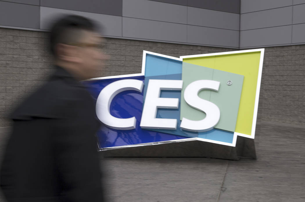 A man walk past a CES sign outside the Las Vegas Convention Center during setup for the convention on Monday, Jan. 8, 2018, in Las Vegas.