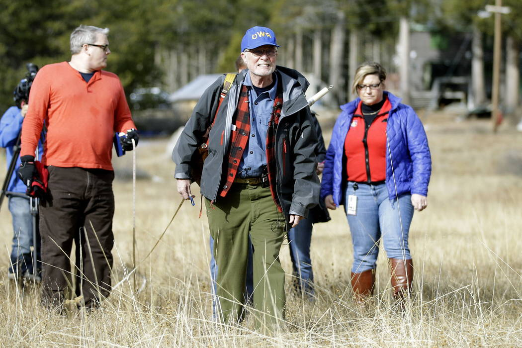 Frank Gehrke, center, chief of the California Cooperative Snow Surveys Program for the Department of Water Resources, crosses a nearly snow barren meadow while conducting the first snow survey of  ...