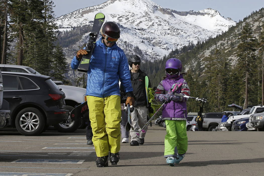 Bret McTigue, left, and his daughter Taylor, 8, head to the slopes at Sierra-at-Tahoe Ski Resort, Wednesday, Jan. 3, 2018, near Echo Summit, Calif. (AP Photo/Rich Pedroncelli)
