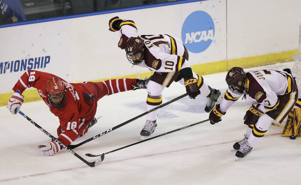 Boston University forward Jordan Greenway (18) passes the puck while defended by Minnesota-Duluth defenseman Brenden Kotyk (10) and forward Adam Johnson (7) during the third period of the NCAA Wes ...