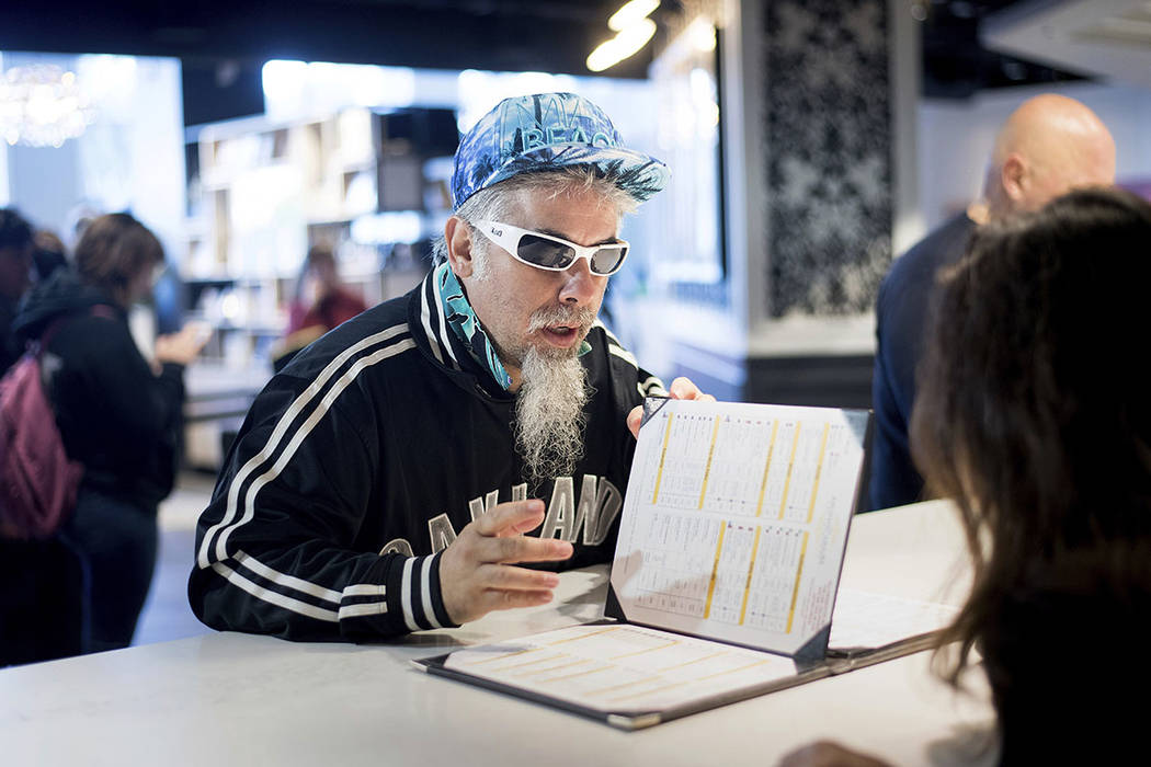 Dominic Rea reads a cannabis menu at The Apothecarium during the store's first day of recreational marijuana sales on Saturday, Jan. 6, 2018, in San Francisco. (AP Photo/Noah Berger)
