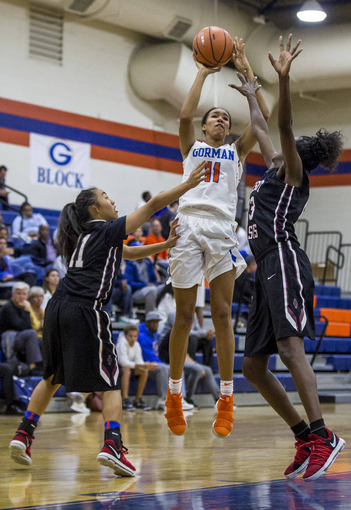 Bishop Gorman's Olivia Smith attempts to put up a point while Desrert Oasis' Kalena Halunajan, left, and Desi-rae Young attempt to block her at Bishop Gorman High School on Friday, Jan. 12, 2018.  ...
