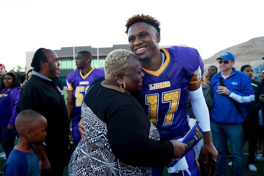 Rissa Wilmore hugs her nephew, Marcus Phillips jr., of Cimarron-Memorial High School, after receiving the Most Valuable Player award after the Lions All-Star football game at Bishop Gorman High Sc ...