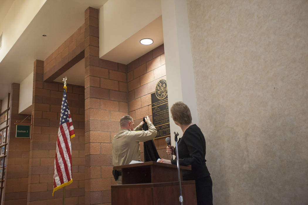 Judge Natalie Tyrrell watches Officer David Cox pull off the cloth over a plaque to commemorate to life of Chad Parque at a memorial at North Las Vegas Justice Court in Las Vegas, Tuesday, Jan. 9, ...