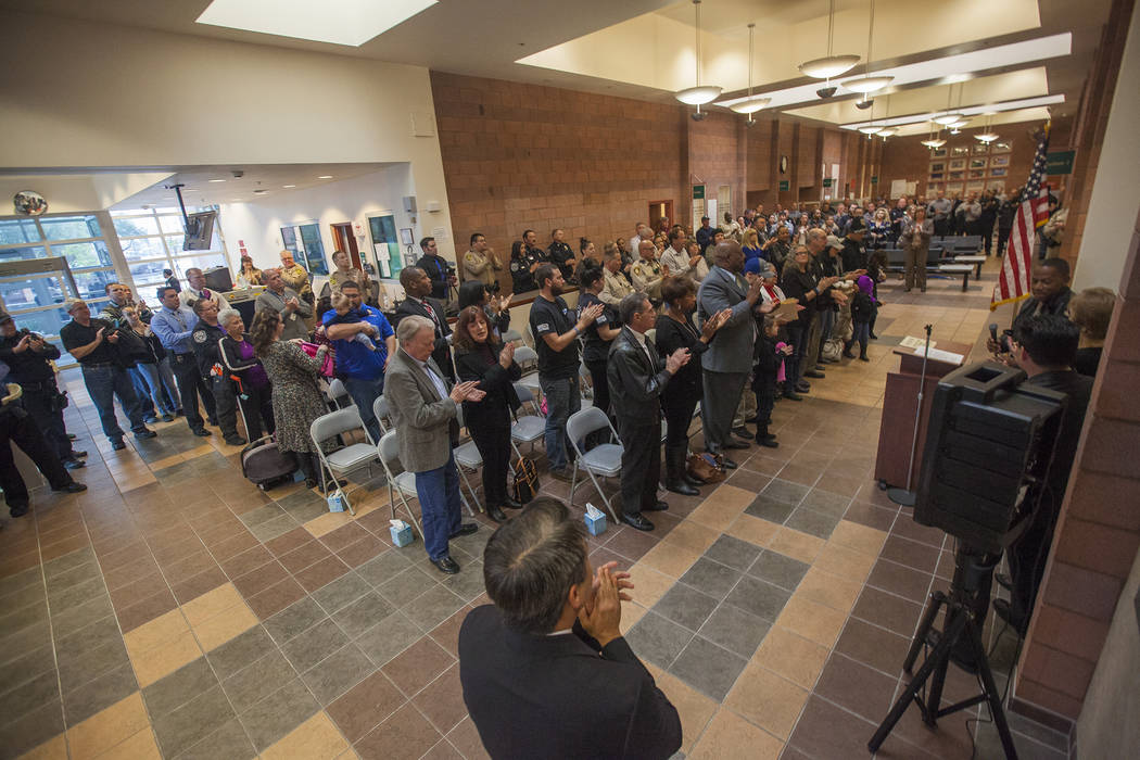 Clark County Commissioner Lawrence Weekly leads an applause to honor Detective Chad Parque at a memorial at North Las Vegas Justice Court in Las Vegas, Tuesday, Jan. 9, 2018. Parque was killed one ...
